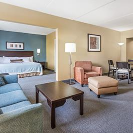 A spacious king suite with a large couch, armchair, leg rest and a mini kitchen in the Wyndham Hotel in Regina