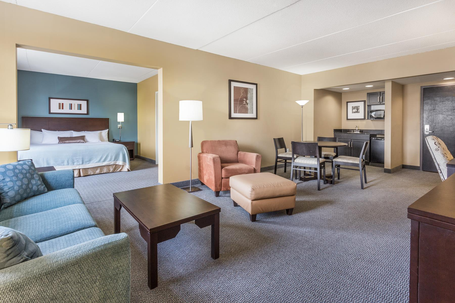 A spacious king suite at the Wyndham Regina SK resort with a mini kitchen and quality furnishings