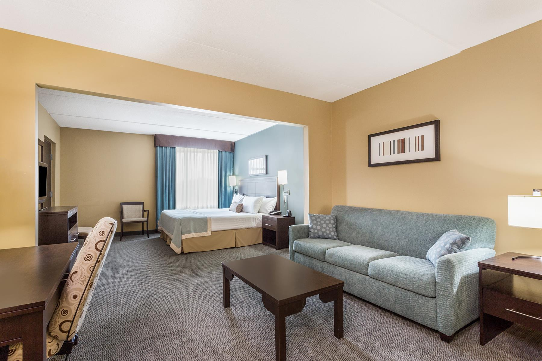 A spacious King hotel room with a TV, large couch , and work desk in the Wingate by Wyndham Resort in Regina SK