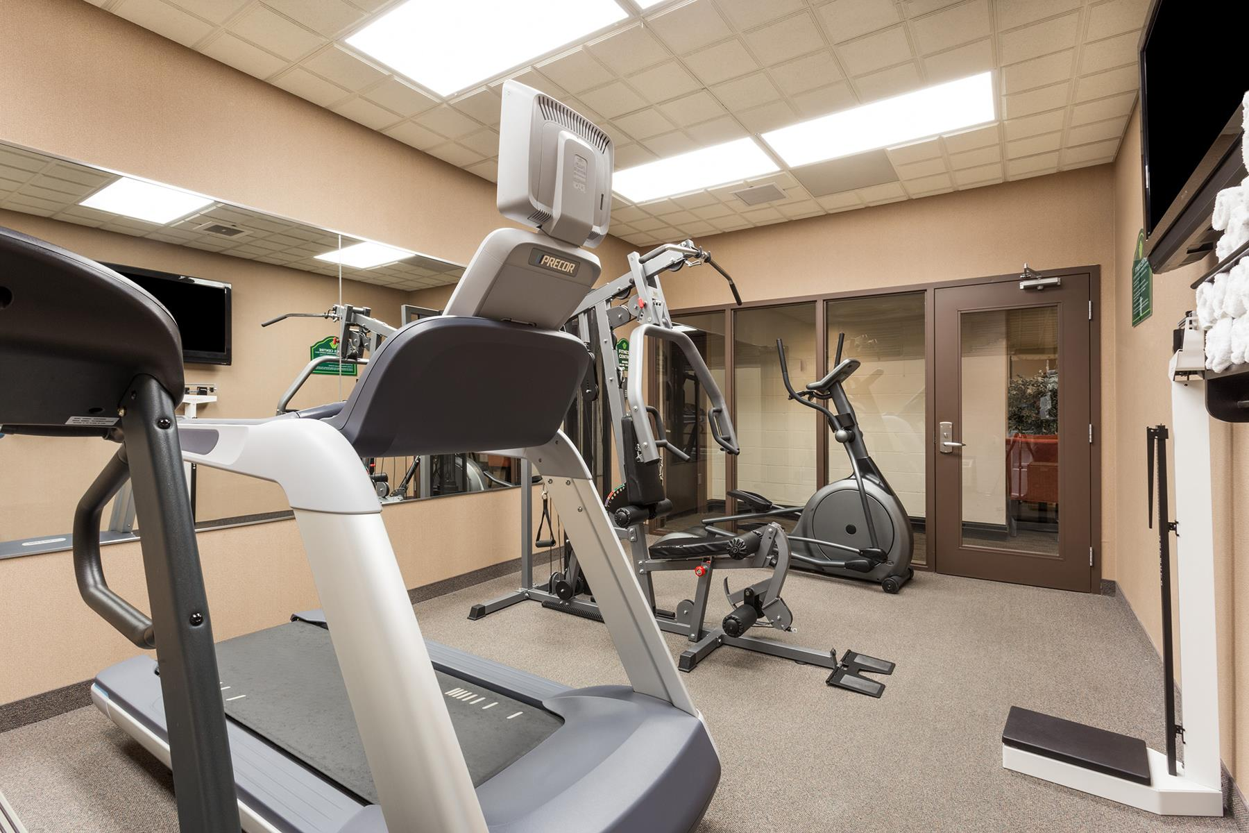 An exercising room with treadmills, a bike and a lifting machine in the Wingate by Wyndham hotel in Regina SK
