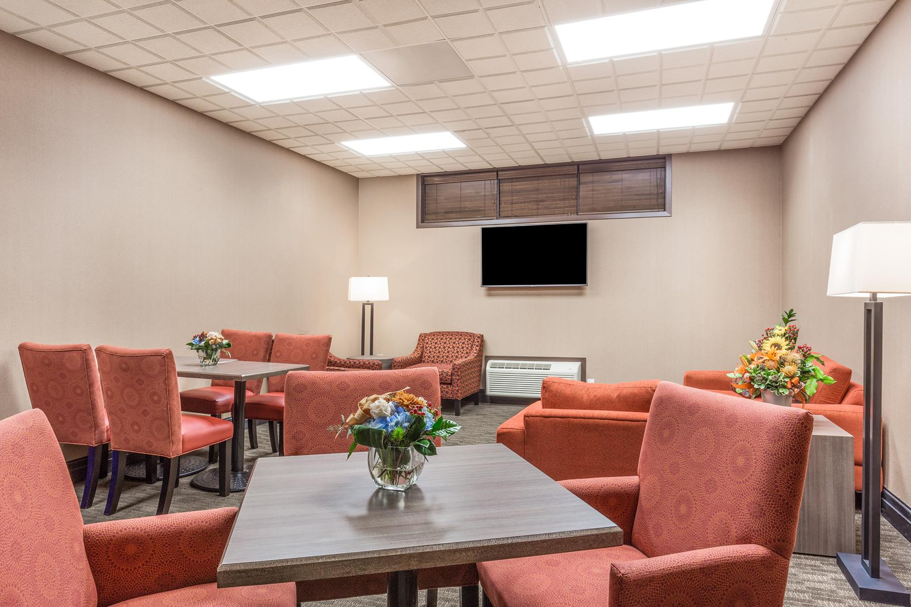 A lounge room with a tv and armchairs where one can relax in the Wingate by Wyndham resort in Regina SK
