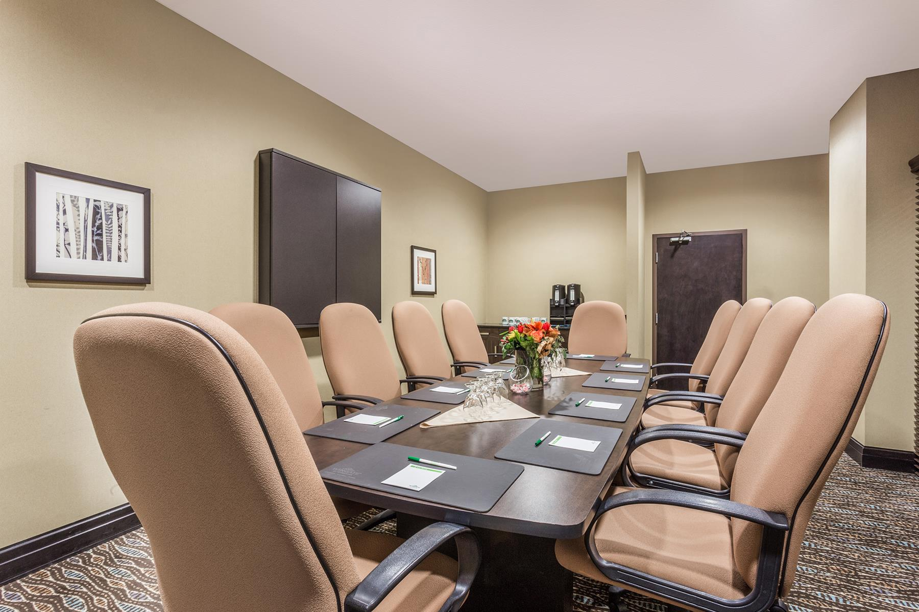 A spacious meeting space with a rectangular table in the middle at the Wingate by Wyndham Resort